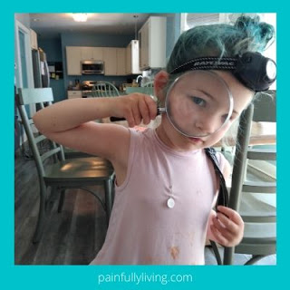 Young girl  with hair in messy bun, wearing a headlamp & using an magnifying glass