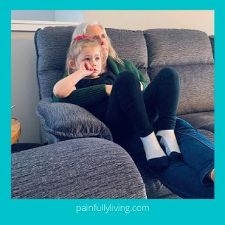 Grandmother cuddling granddaughter on a couch