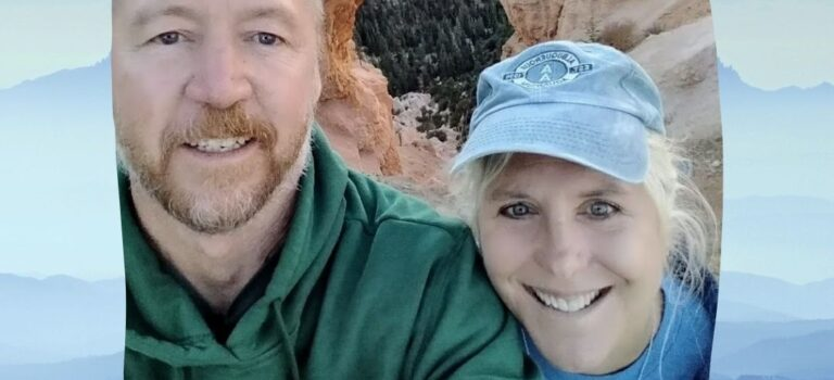 A smiling man and woman infront of a natural arch in Arches National park.