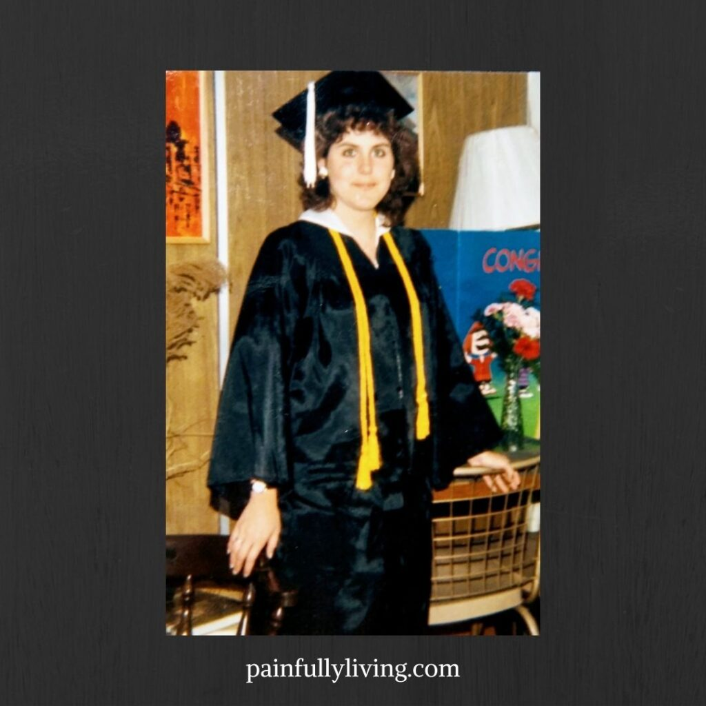 Smiling young woman with curly dark brown hair, wearing black college graduation robe and mortarboard with gold honors tassels. In the background a brown wall with painting, table and chair.
