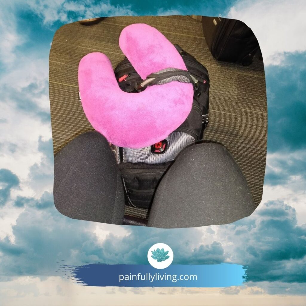 Seated in the airport, image of knees in black pants, with black backpack and hot pink fuzzy half-moon headrest.