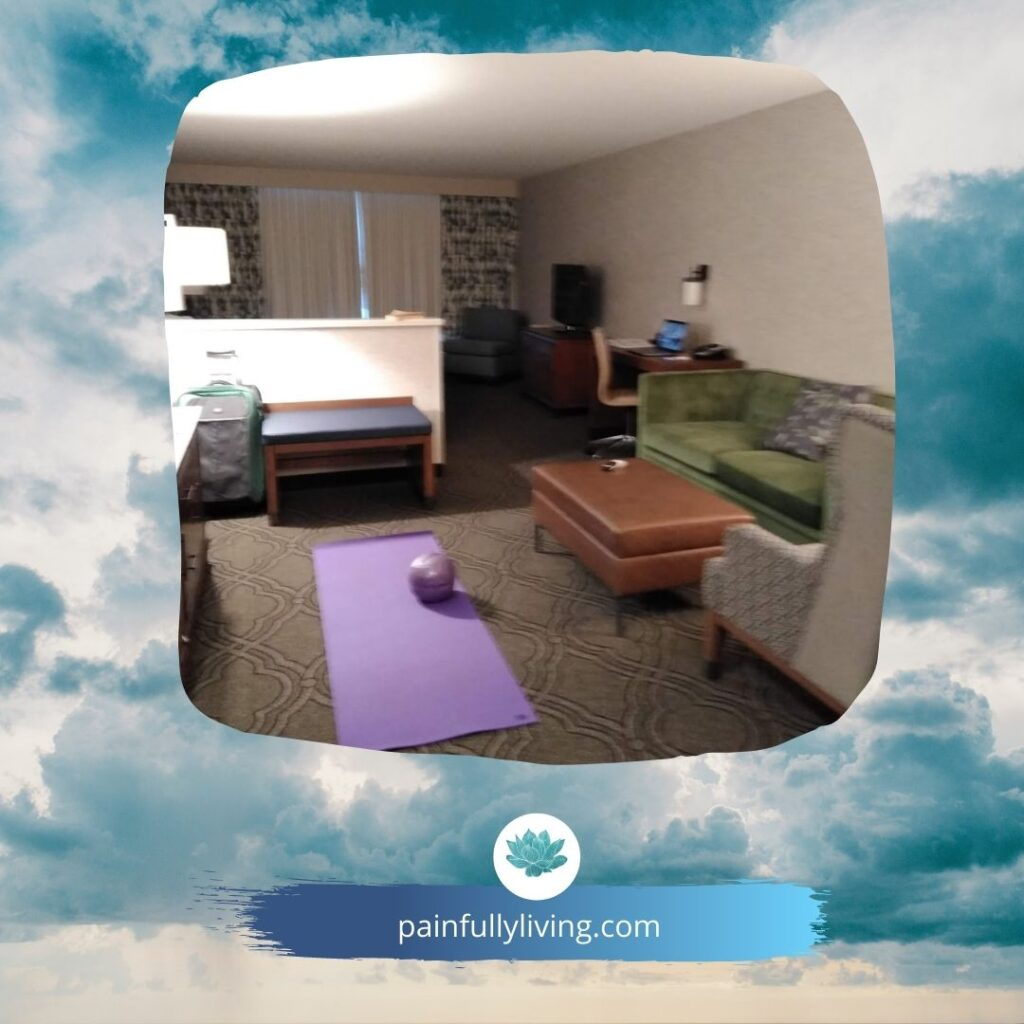 Image of a hotel room with sitting room, purple yoga mat on the carpeted with purple Coreageous ball on it.