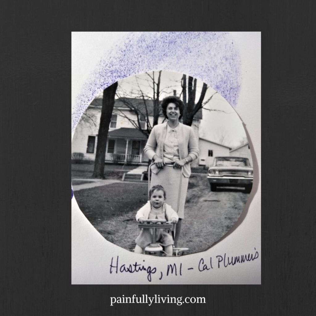 Black and white photo with young mom, with large smile and two piece skirt and cardigan outfit (1964) pushing a happy baby wearing a white sweater in a stroller. Background is a white house with front porch and car parked in the dirt driveway.