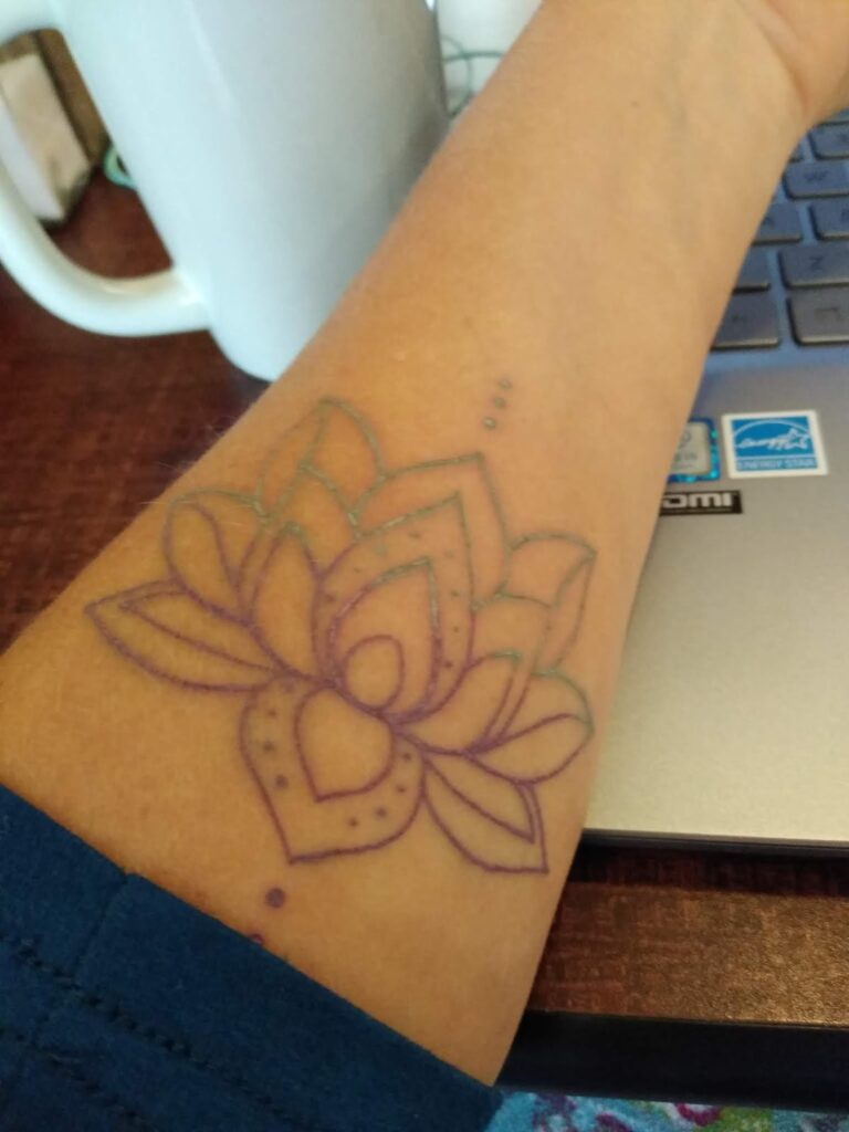 Photo of my inner forearm laying on my computer keyboard, white coffee cup behind it.  On my forearm is an outline of a lotus flower done in purple and teal colored lines and dots.