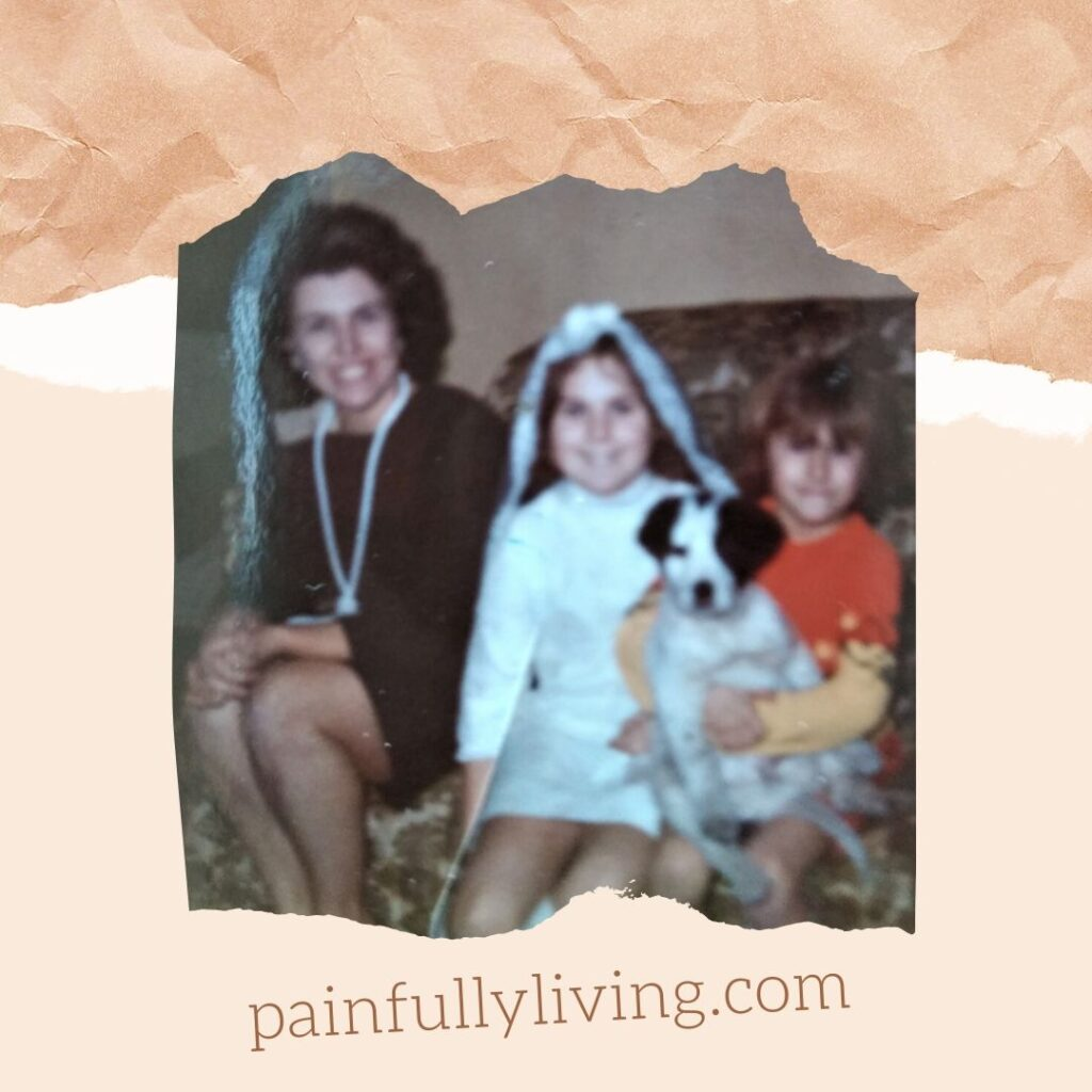 Sitting on a floral-patterned couch, my mom is smiling, brown styled curly short-hair, red lips, brown dress with long white necklace. I'm next to her in an all knee-length, white 1st-communion dress and white vail with.  Chin length, straight brown hair, smiling to the camera.  My 4-year-old sister is sitting next to me, light brown hair with bangs nearly covering her eyes.  She's holding our black and white pup, his chubby belly showing.
