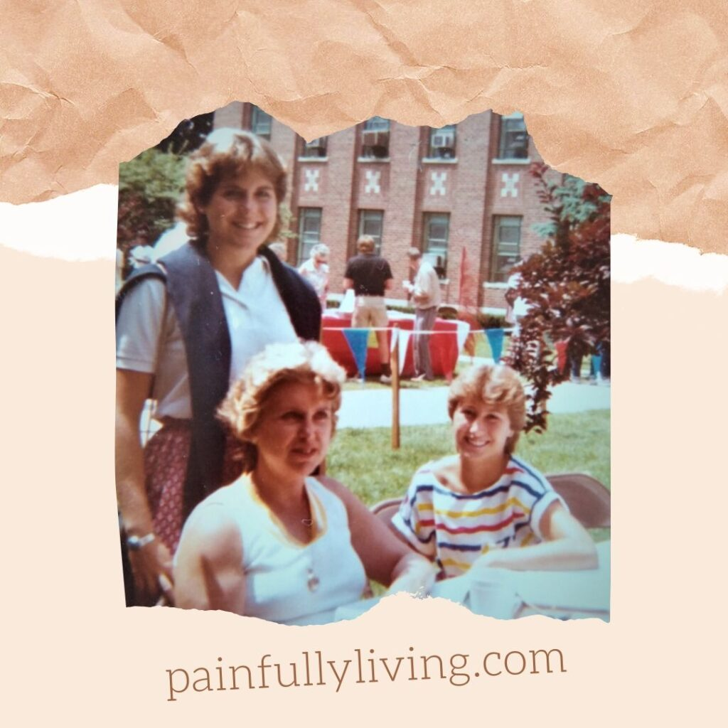 Sitting outside of a huge brick building (Kalamazoo State Hospital) at a white folding table, my mom is noticibly gained weight and her dark brown hair is now lighter and unkempt (still in her Elizabeth-Taylor style, though). My 14-year old sister wearing a bring striped top is sitting next to her, her light-brown hair in a short-style with winged bangs is smiling.  I'm standing behind my mom (16 yrs), hand on the back of her chair, smiling. I have dark, curly hair cut in a shag-style.  I'm wearing a white polo with a blue sweater draped around my shoulders.