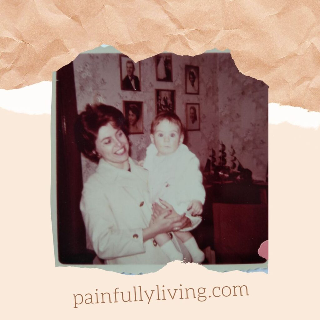 Image of my mom (28), wearing an all white skirt suite (that she made), smiling and holding me at age 6 months wearing all white outfit made from the scraps of her suit. She is standing in the living room of her parents home, in the background are the photos of her 5 siblings and herself.