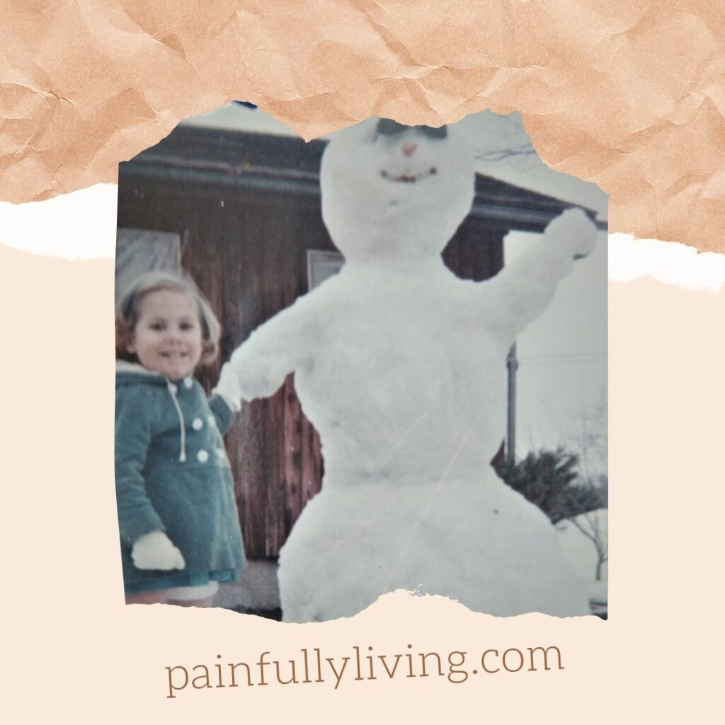3-year-old me standing next to a huge snowman double my height.  My hair is chin length, curled under, wearing a blue headband. I'm wearing a blue corderoy winter jacket with white buttons and white wool lined hood and white mittens.  I am wearing a dress, with bare legs, but tall red boots. I'm touching the snow arm of the snowman, as if holding his hand.  He has sunglasses, carrot nose, and pebble mouth and has his other  snow arm raised up as if waving hello.