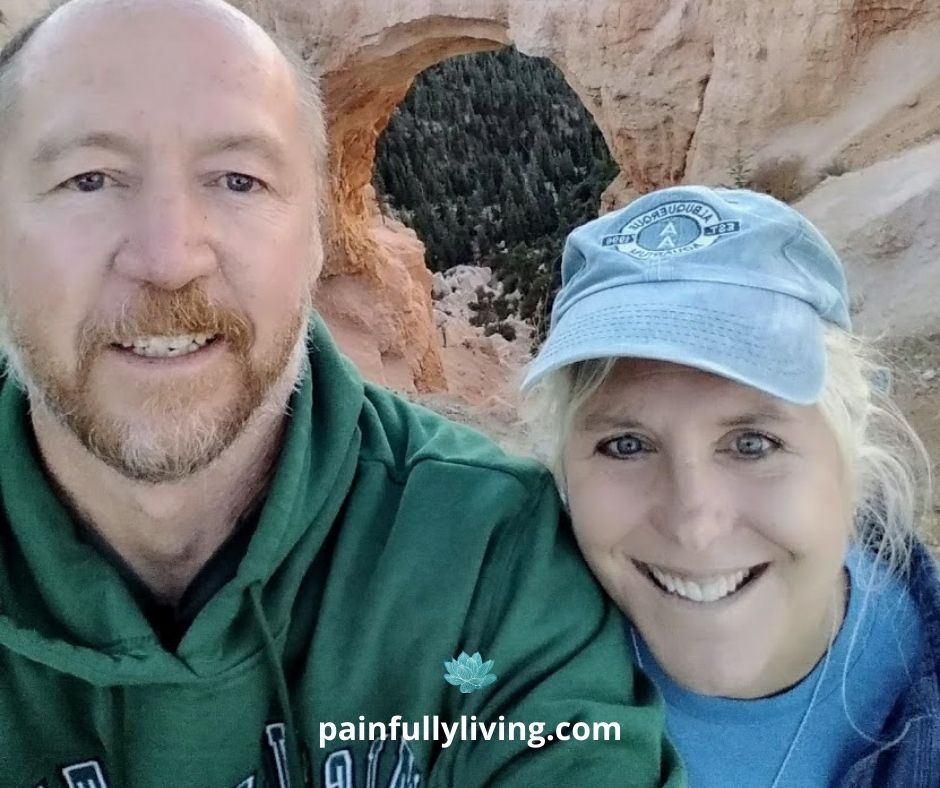 Smiling man with redish beard and little hair on his head is taking a selfie with smiling woman wearing a blue baseball cap.  Behind them is a red sandstone Natural Bridge of Bryce National Park.