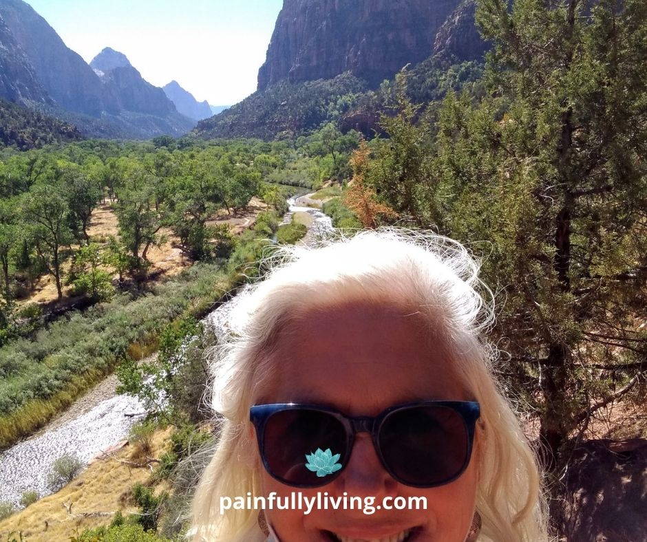 Smiling woman's face; she's wearing dark sunglasses and has her white hair pulled back off from her forehead.  In the background is a river, trees, and mountains.