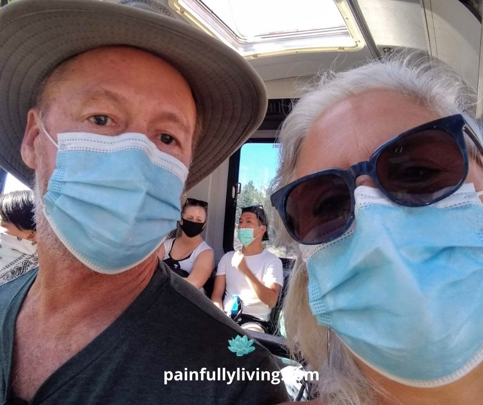 Man wearing a blue hospital mask with a wide brimmed hat, next to a woman with white, long hair wearing dark sunglasses and blue hospital mask, in front of seated people wearing masks.