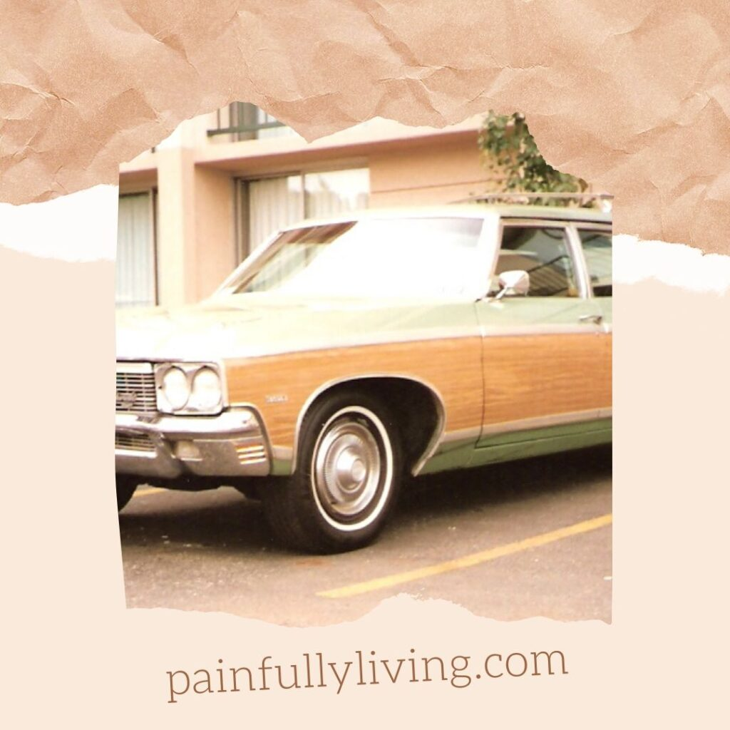A wood-paneled, light green station wagon circa 1970s parked in a driveway in front of a garage door.