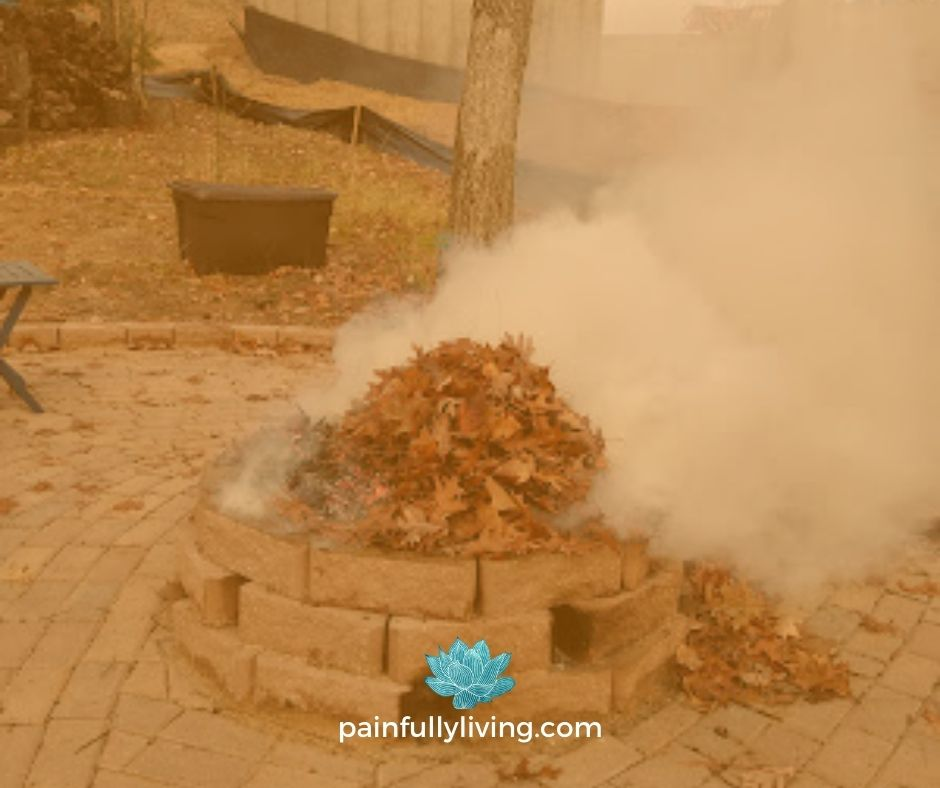 A pile of fall oak leaves burning and smoking in a bricked fire pit.