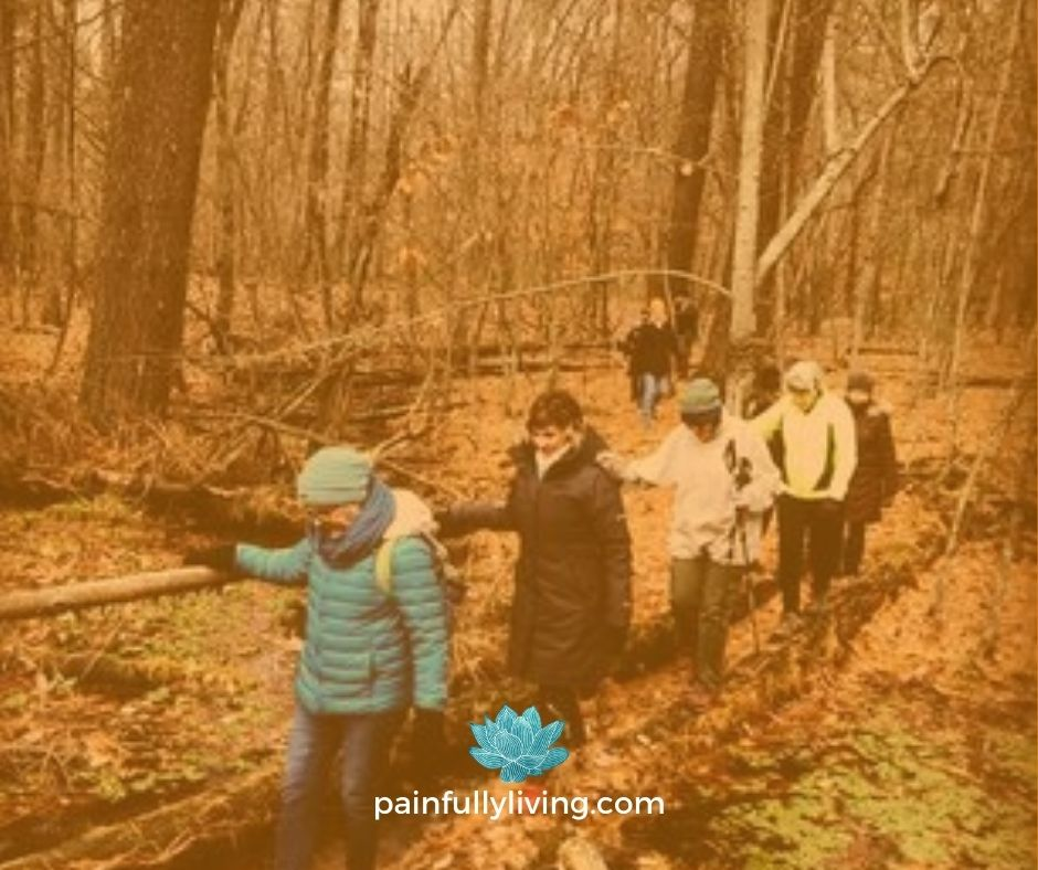 A group of women, dressed in winter gear, walking on a in a row through a leaf covered forest floor.