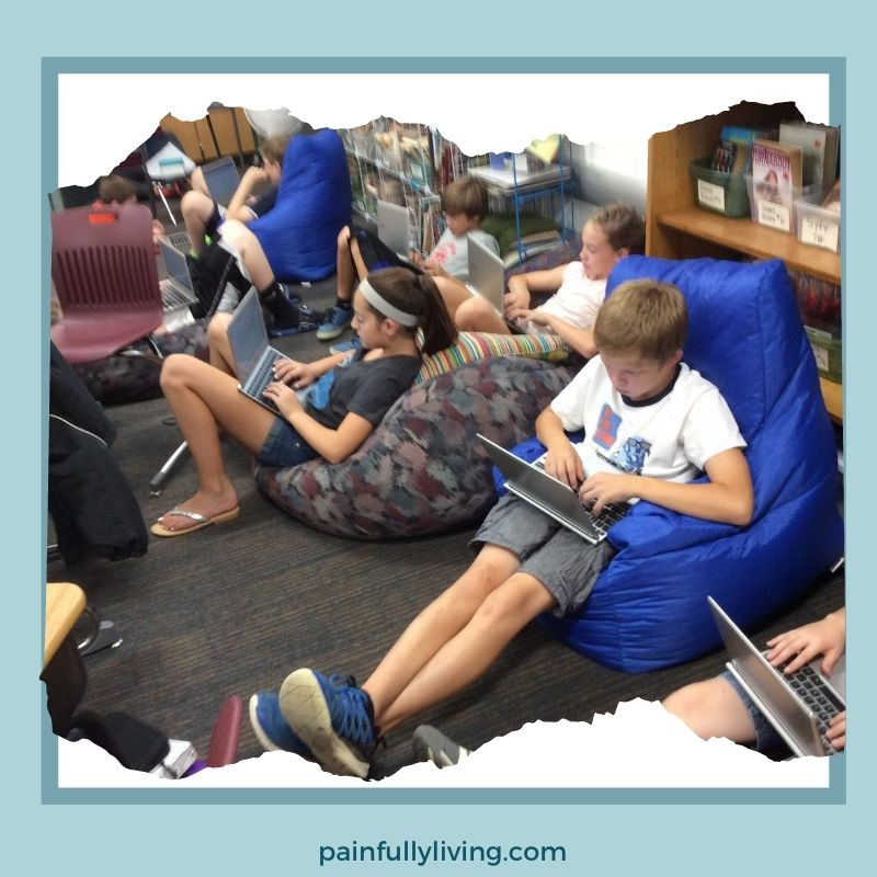 Students scattered on the classroom floor, sitting in bean bag chairs and pillows among the shelves and shelves of books, typing on their Chromebooks.