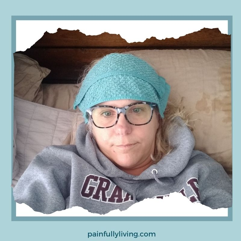 Me, obviously not feeling well, laying in bed with a cold, wet washcloth on my forehead.