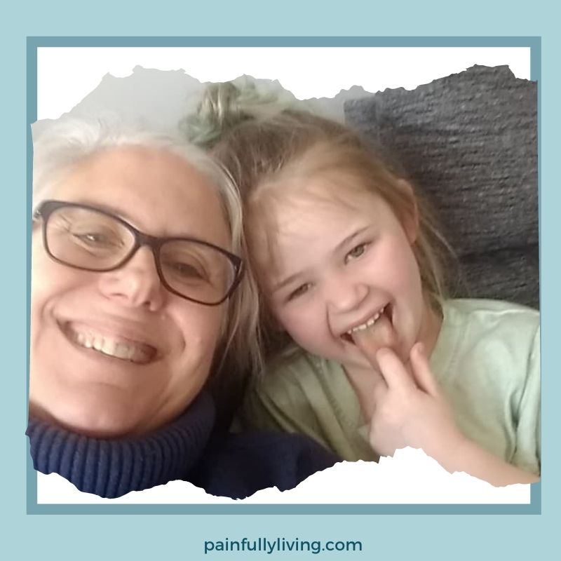 Me, smiling with my head touching my 5 -year old granddaughter's head as we sit on the couch together.