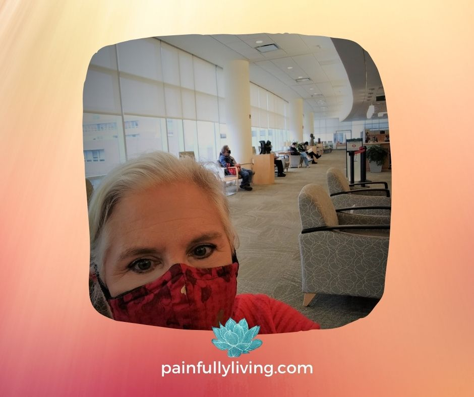 Me wearing a red mask and orange sweater, sitting in a spacious waiting room at the Michigan Cardiology Center.