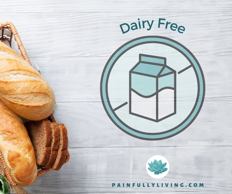 A white-washed wood plank background with whole loaves of bread in the lower left corner.  Off set to the right is a graphic of a milk carton in the middle of a circle with a line diagonally through it. Above the circle is the text Dairy Free in dark teal font.