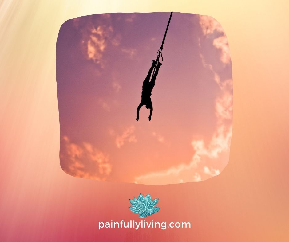 Image of person upside down attached at the ankles by a bungee cord-orange sunset background.