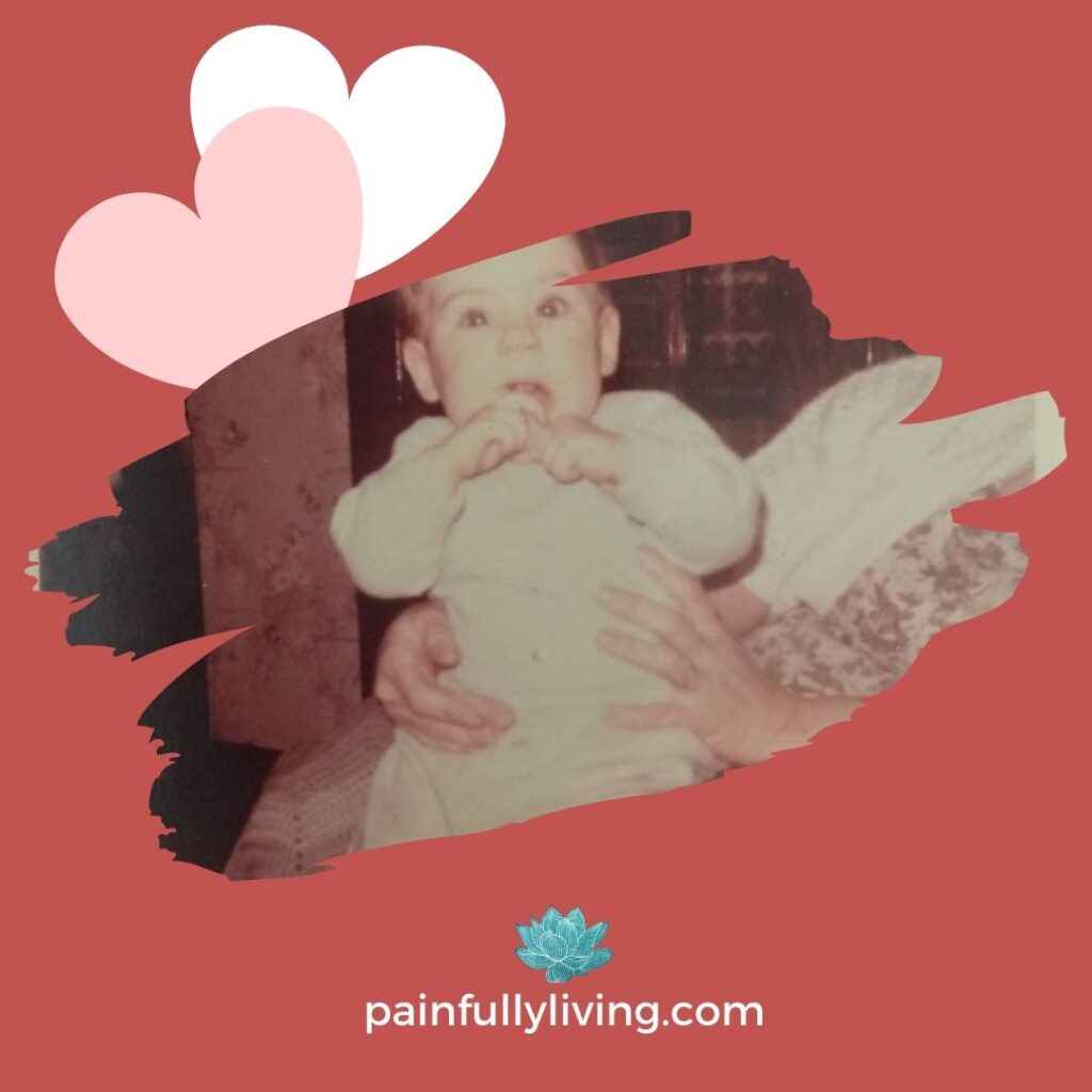 A 6 month old baby (me) sitting the lap of an older woman (my grandmother).  Background red with two hearts in the top right corner.