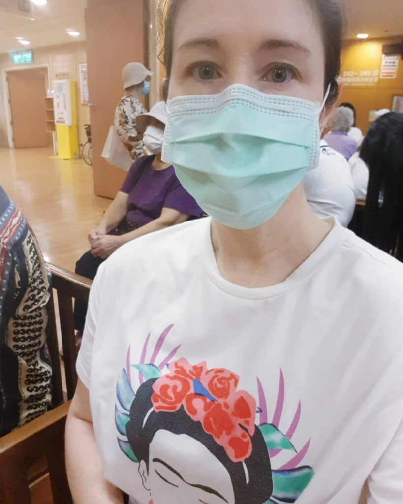 Carrie Kellenberger, wearing a mask, hair pulled back, eyes looking pained, sitting in a full waiting room in a hospital. Life with Chronic Illness