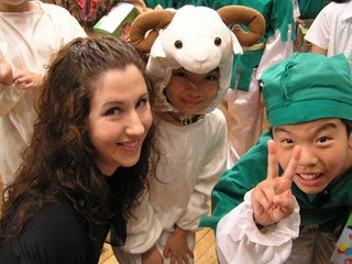 Carrie Kellenberger, smiling and long dark hair, surrounded by young children who are in her REACH TO TEACH program in Taiwan.