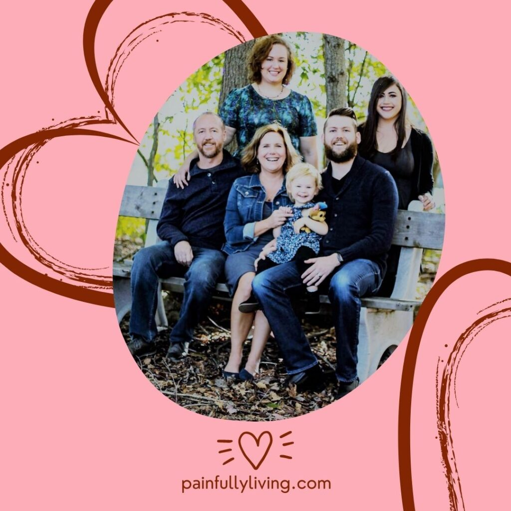Image of my family: Kelley on a park bench in the woods is sitting next to me, holding our granddaughter.  My son sitting next to me.  Behind us is my daughter and daughter-in-law.  The background is pink with  abstract heart lines in burgandy.