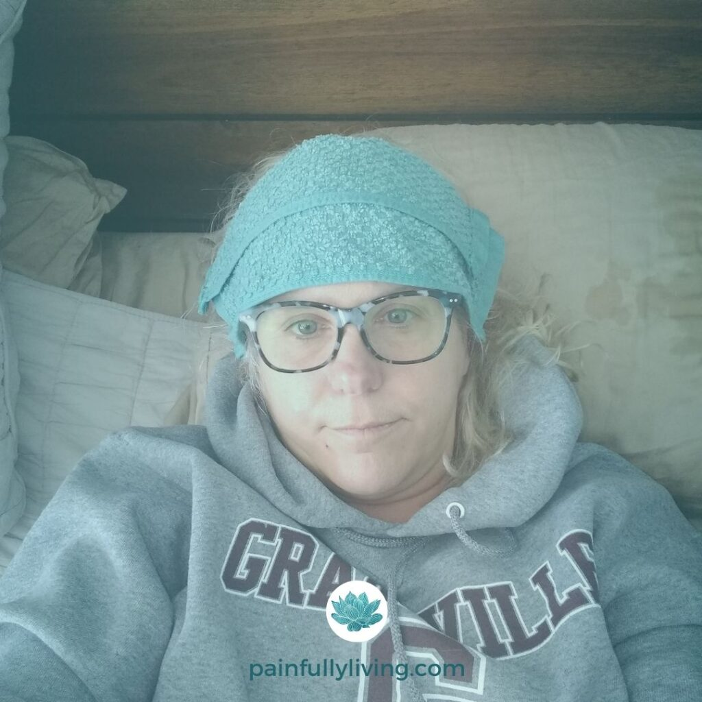 Me, in bed, wearing my grey comfy hoody and a cool, wet washcloth over my forehead.  I'm in visible pain.