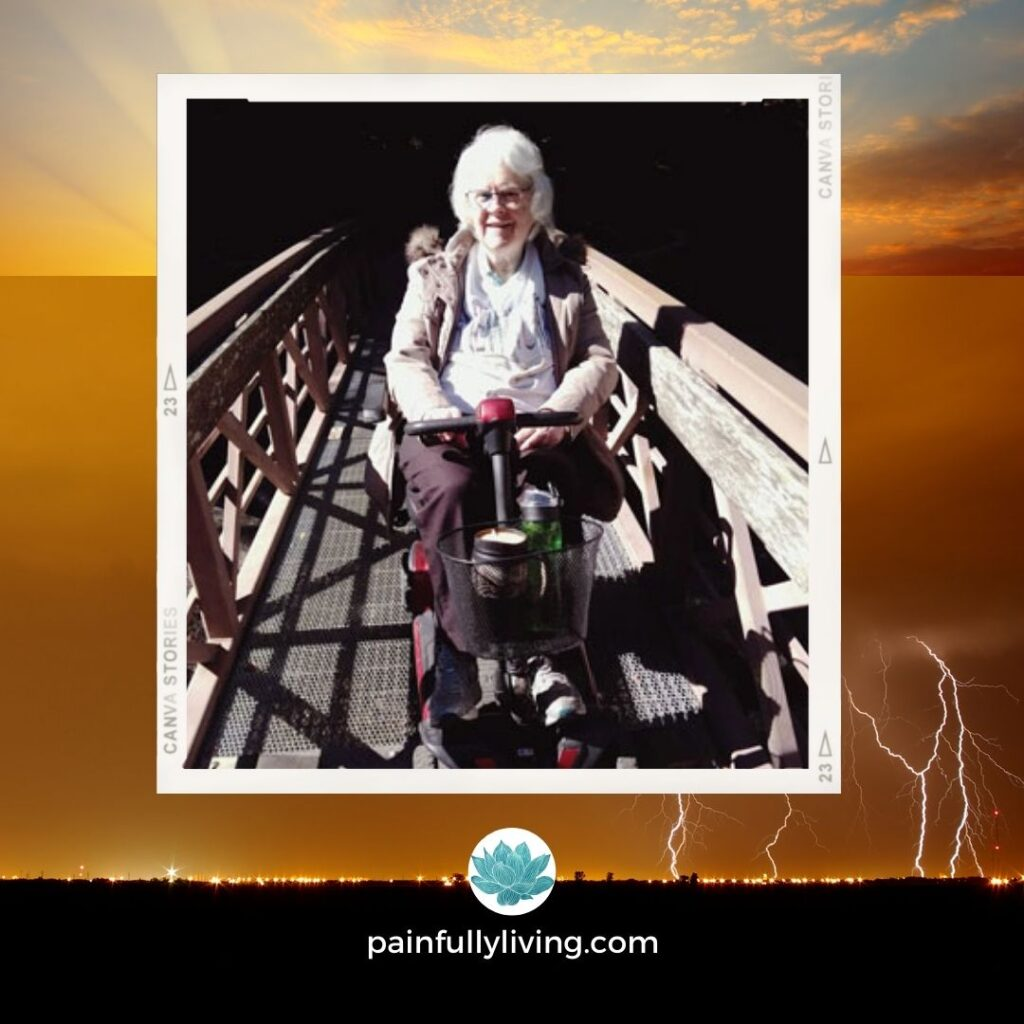 Carole in a power wheelchair on a wooden bridge.  Background of clouded lightening storm with sun rise and blue skies opening up.